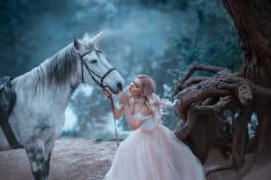 A fairy in a tender vintage dress hugs a unicorn. Fantastic magical, radiant horse. Background river and forest. Blonde girl with wavy hair - light elf. Artistic Photography