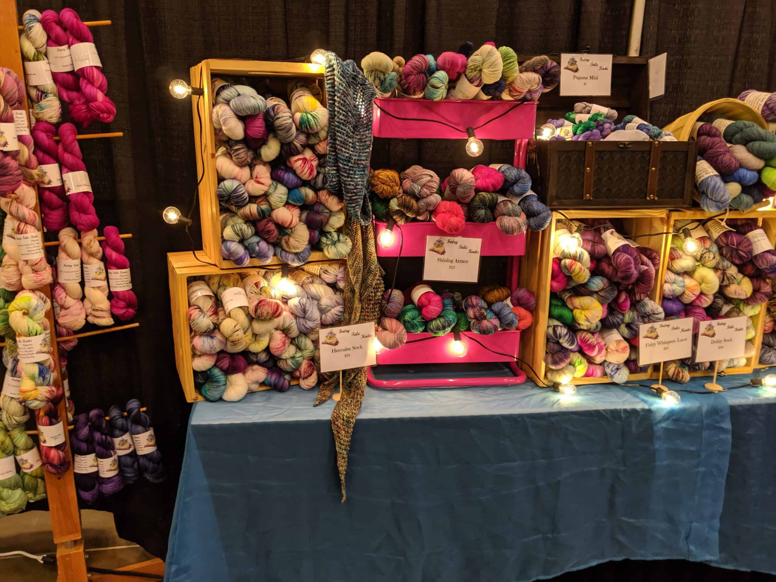 Hand dyed yarn in crates on a table at a fiber festival